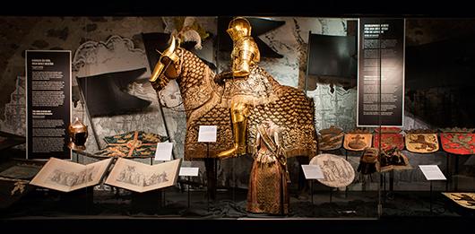 """Från vänster, bl a : Gustav Vasas """"vapenkjortel"""", en krönt hjälm och en häroldskåpa. Bars på stång i processionen 1560. Den gyllene """"kyritsryttaren"""". Framför denne - hyllningsdräkt för 4-årige tronarvingen, prins Karl (XI), en ceremoniell kolt av purpurfärgad gyllenduk. Barnsadel i svart sammet och silverspetsar för prins Karl (XI) och ett antal landskapssköldar. Foto: Jens Mohr"""