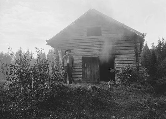 Johan Olssoni Röjdfors framför sin bastu. Bastun saknar skorsten. Röken tränger ut från dörröppningen. Foto: Astrid Reponen 1930, Museiverkets bildsamlingar SUK334 70