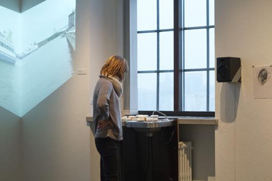 VASKA av Emelie Röndahl ljudsätts av den droppande kranen. På väggen en detalj av videon RITE DE PASSAGE av Jasmine Lyman i samarbete med luftakrobaten Milla Floryd. Foto: Sjöfartsmuseet/Akvariet