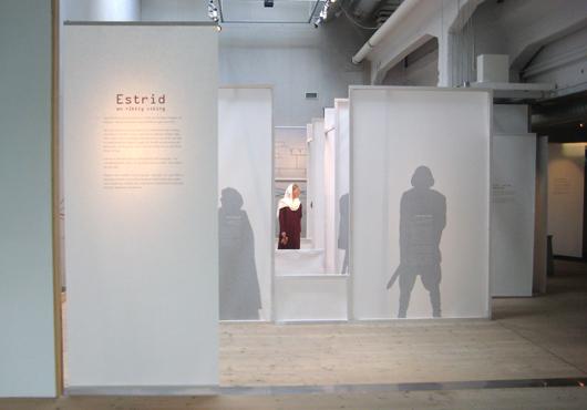 Estrid står mitt i rummet, omgiven av sin familj.