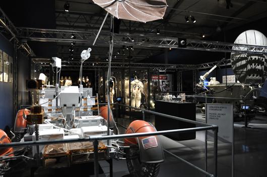 Tekniska triumfer fyller utställningsrummen. Till vänster en månbil. I mitten syns några rymddräkter.