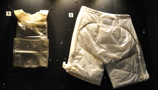 Till höger syns den blöja som astronauten måste bära och till vänster den fekaliepåse som ersatte toaletten.