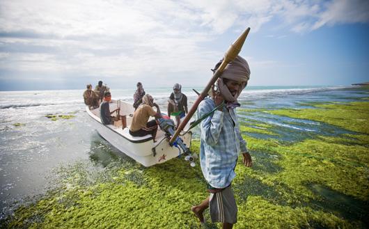 """Piratledaren Abdul Hassan, Somalia, bär på en granatkastare. Den här gruppen pirater kallar sig """"Central Regional Coast Guard"""". Foto: Veronique de Viguerie"""