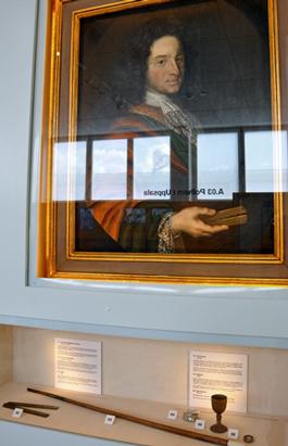 Under porträttet av Polhem syns en proportionalcirkel likadan som den han håller i handen, hans käpp och snusdosa, en bägare och en medaljong.