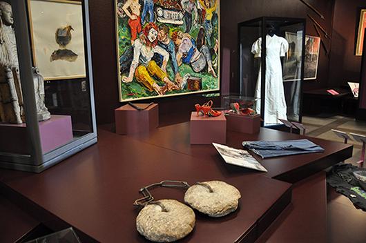 """I förgrunden syns tortyrredskapet """"stadens stenar"""". Bakom skymtar bl.a. ett par kinesiska kvinnoskor, ett par svenska kvinnoskor, en medeltida madonna i romansk stil, Elin Wallins brudklänning från 1905, ett par jeans från Gul & Blå och Albin Amelins oljemålning """"Raggare""""."""