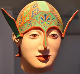 Huvud av krigare från Afaiatemplets östra gavelfält. Kindskydden är uppvikta som glada vingar och mönstret påminner om folklorististiska dekorationer.