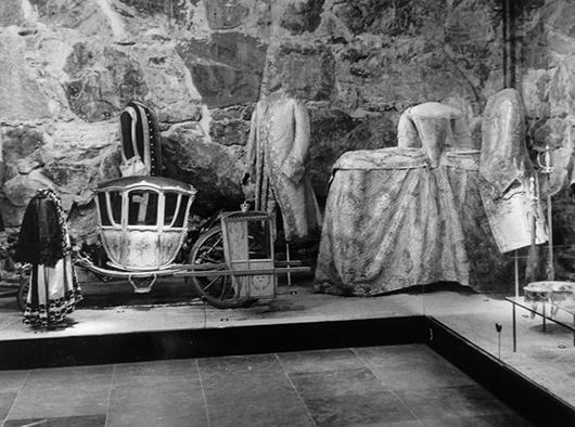Drottningars och prinsessors kläder började sparas först vid mitten av 1700- talet, och var sällsynta i den ursprungliga basutställningen. I denna scenbild dominerar museets första klänning, drottning Sofia Magdalenas brudklänning i blommig silverbrokad broderad med knypplade silverspetsar och, för säkerhets skull, omgiven av tre av maken, Gustav III:s kostymer, längst t v serafimerkolt för den tvåårige kronprinsen, hans myndighetsdräkt och slutligen, hans i Paris sydda bröllopsdress i silverbrokad, broderad med guldtråd och blåskimrande paljetter. I Paris hade 40 personer dag och natt i nära 4 veckors tid arbetat med dressen. Det blev en engångsdräkt. Den händelserika scenbilden utspelar sig mot en vägg av murad grovhuggen gråsten och ett golv av slitstark, gotländsk kalksten.