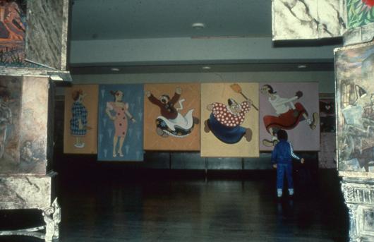 Feministiska Vi arbetar för livet ställdes ut på Liljevalchs konsthall 1980. I Riksutställningars turnéversion blev det en av de mest älskade vandringsutställningarna under det kommande året. Genom förgrundens installation av Lotta Hagerman och Ewy Palm ser man Satkärringar porträtterade av Lilian Ek och Kerstin Boulogner. Foto: Riksutställningar