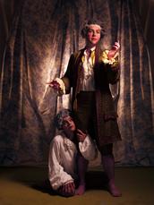 Gustav III står i teatralisk pose med smink i ansiktet och en exalaterad min. Han än barfota och de knälånga byxorna blottar oväntat kraftiga vader, han ser kraftfullare ut än den traditionella bilden av honom som späd och anemisk. Hans page har slingrat sig runt hans ena ben och tittar drömmande uppåt. Foto: Elisabeth Ohlsson Wallin