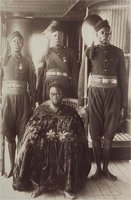 Oba Ovoranmwem ombord på det brittiska örlogsfartyg som förde honom i exil efter invasionen 1897. Han bär inga tecken på kungavärdighet utan är höjd i en mantel och hans fötter är kedjade. Bakom honom står tre vakter med gevär.
