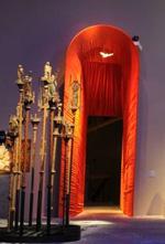 Genom ett blodrött  tygdraperat valv gör man entré i Mariautställningen, för tillfället blåtonad.